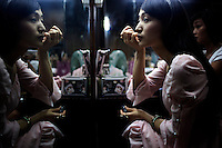 Dancer and singer Lin Yan applies makeup prior to taking part in a performance at The West Lake Restaurant. Able to seat up to 5,000 people at one sitting, The West Lake Restaurant is the biggest Chinese restaurant in the world. Each week its diners, who staff are taught are 'the bringers of good fortune', devour 700 chickens, 200 snakes, 1,200 kgs of pork and 1,000 kgs of chillis. Its 300 chefs cook in five kitchens and its staff total more than 1,000.It is fully booked most nights.