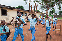 Nigeria. Enugu State. Enugu. Army Day Secondary School ( Awkunanaw in Igbo language). Classroom. A group Igbo students carry stools in the school's courtyard. All pupils wear blue uniforms and are 12-13 years old. They belong to Junior Secondary School. The Army Day Secondary School was inaugurated in October 1998. Enugu is the capital of Enugu State, located in southeastern Nigeria. 11.07.19 © 2019 Didier Ruef