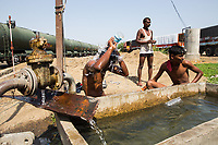 Men have a wash in a trough at the Latur train station. With a very limited supply of water, residents of the city are forced to reduce the number of times they wash and clean.