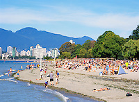 Crowded Kitsilano Beach in Summer, Vancouver, BC, British Columbia, Canada - West End and North Shore Mountains (Coast Mountains) beyond