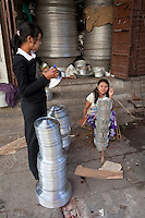 Myanmar, Burma, Mandalay.  Two Young Women about to Carry a Load of Metal Dishes and Utensils.