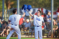 South Dakota State Jackrabbits designated hitter Luke Ira (1) celebrates with Jamie Berg (right) after hitting a home run during a game against the Northeastern Huskies on February 23, 2019 at North Charlotte Regional Park in Port Charlotte, Florida.  Northeastern defeated South Dakota State 12-9.  (Mike Janes/Four Seam Images)