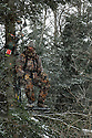 00105-042.16 Bowhunting (DIGITAL) Archer is in tree stand in balsam fir during snow storm.  Hunt, cold, late season, deer, winter.  V5R1