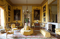 The yellow drawing room, with its striped, golden yellow walls and matching soft furnishings. State portraits of King George III and Queen Charlotte by Alan Ramsay flank the doorway