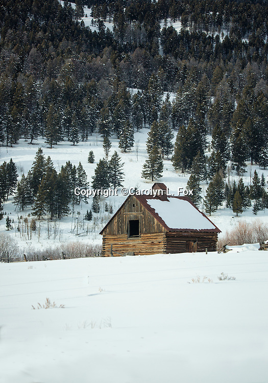 An old barn sits in the snow.