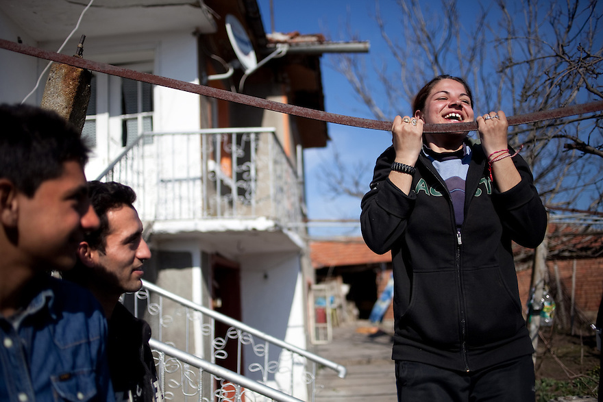 Prohorovo, Bulgaria, Kalaidzhi--Todorka Dimitrova, 18, right, showing her strength as she jokes with Bozhidar Petrov, 17, and Giorgi Nikolov, 24 who came to inquire about her as a bride. They are members of the Kalaidzhi, a subset of the Roma people whose 20,000 are dispersed throughout Bulgaria.