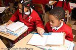 K-8 Parochial School Bronx New York Grade 3 mathematics lesson on measurement using rulers boy and girl working ad desks horizontal