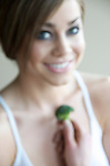 Young woman with bare shoulders eating healthy vegetables.
