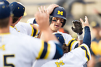 Michigan Wolverines third baseman Jake Bivens (18) is greeted by his teammates after scoring against the Eastern Michigan Hurons on May 3, 2016 at Ray Fisher Stadium in Ann Arbor, Michigan. Michigan defeated Eastern Michigan 12-4. (Andrew Woolley/Four Seam Images)