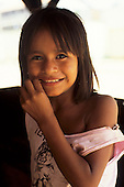 Amazon, Brazil. Smiling girl chewing on a twig. Acre State, near the Peru border.