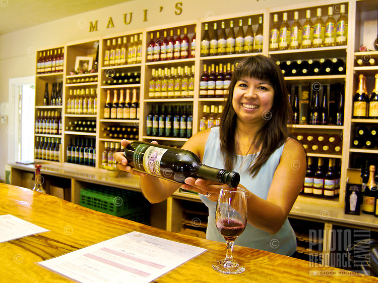 Pouring wine in the tasting room (The King's cottage, built for frequent visitor King David Kalakaua) at Tedeschi Winery, a historical site on the outer slopes of dormant Haleakala volcano, Upcountry Maui. Tedeschi is known for its pineapple wine, a