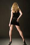 Caucasian blonde woman facing away from camera on black seamless