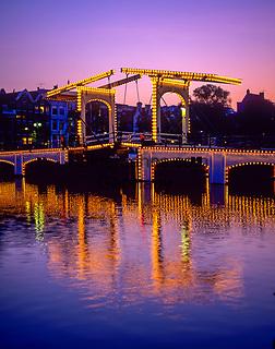 Niederlande, Nordholland, Amsterdam: Bruecke Magere Brug an der Amstel am Abend | Netherlands, North Holland, Amsterdam: Skinny Bridge (Magere Brug) on the Amstel at dusk