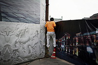 """CHINA. Beijing. A man climbs over a fence, trying to catch a glimpse of the new Qianmen shopping district. In recent years construction has boomed in Beijing as a result of the country's widespread economic growth and the awarding of the 2008 Summer Olympics to the city. For Beijing's residents however, it seems as their city is continually under construction with old neighborhoods regularly being razed and new apartments, office blocks and sports venues appearing in their place. A new Beijing has been promised to the people to act as a showcase to the world for the 'new' China. Beijing's residents have been waiting for this promised change for years and are still waiting, asking the question """"Where's the new Beijing?!"""". 2008"""