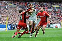 George Lowe of Harlequins is tackled by Alex Goode of Saracens as Charlie Hodgson of Saracens looks on during the Aviva Premiership match between Saracens and Harlequins at Wembley Stadium on Saturday 31st March 2012 (Photo by Rob Munro)