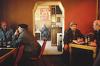 Bulgaria. Province Oblast Lovech. Lukowit. Men seat in a restaurant. They drink beers and talk together. A man smokes a cigarette. A single old woman seat in another dining room. A Coca Cola advertising poster is taped on a wall.  © 1997 Didier Ruef