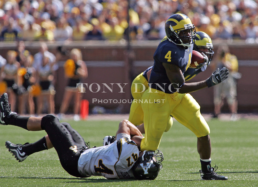 1 September 2007: Appalachian State defensive back Cory Lynch hangs onto the foot of Michigan running back Brandon Minor in the 2007 season opener college football game between the Michigan Wolverines and Appalachian State Mountaineers at Michigan Stadium in Ann Arbor, MI. No. 5 ranked Michigan was upset 32-34.