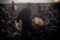 O trabalho no maior lixão da América Latina <br /> Num dos símbolos do patrimônio cultural da humanidade, a cidade Brasília mantém trabalhadores em situações insalubres e de risco, em atividade no maior lixão da América Latina.<br /> Brasília tem a maior renda per capita do País, mas não sabe cuidar do próprio lixo e ainda mantém o lixão da Estrutural, uma vasta área a 16 km do Palácio do Planalto, sede do governo federal, que é inundada diariamente pelos resíduos sólidos despejados pelos 2,8 milhões de habitantes do Distrito Federal.<br /> Todos os dias, o lixão da Estrutural recebe, em média, 2,7 mil toneladas de resíduos orgânicos e 6 mil toneladas de resíduos da construção civil.<br /> Oficialmente, 1.200 catadores estão cadastrados, mas o governo estima que o número total de pessoas que tiram o sustento dali deve superar 2 mil. <br /> Além das ameaças de contaminação por doenças, esse trabalhadores também estão diariamente expostos a graves acidentes.<br /> Cidade Estrutural, Distrito Federal.<br /> Foto Eraldo Peres/Photoagência<br /> 05/2014