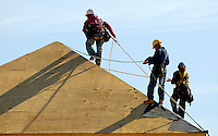 02/22/07:  Construction workers attach plywood to a new roof during expansion/construction of a Charlotte-area shopping center. Charlotte, NC, is one of the country's fastest-growing cities. ..By Patrick Schneider- Patrick Schneider Photography.