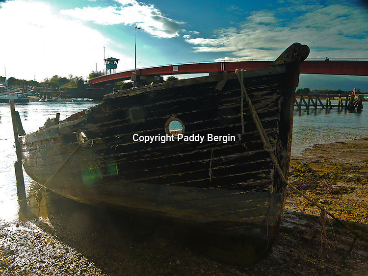 An old boat in need of repair moored on the bank of the River Arun, Littlehampton, West Sussex.<br /> <br /> Stock Photo by Paddy Bergin