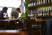Inside a cafe restaurant and wine shop in Paris, La Muse Vin Cave and Bistro, at lunch time. A blurred couple man woman having lunch, a table set for guests and bottles on a shelf in the background.