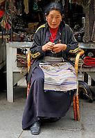 Tibetan handicrafter making yak bone bracelets for sale at her market stall on the Barkhor pilgrim circuit, Lhasa, Tibet.
