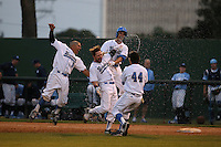 Eric Filia (4) of the UCLA Bruins, second from the left, celebrates with teammates Trent Chatterton (8), Luke Persico (21), Brett Urabe (44) after driving in the winning run in the 9th inning of a game against the North Carolina Tar Heels at Jackie Robinson Stadium on February 20, 2016 in Los Angeles, California. UCLA defeated North Carolina, 6-5. (Larry Goren/Four Seam Images)