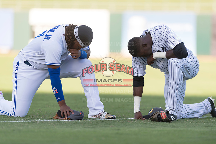 AFL West third baseman Vladimir Guerrero Jr. (27) and outfielder Estevan Florial (13) pray before the Arizona Fall League Fall Stars game at Surprise Stadium on November 3, 2018 in Surprise, Arizona. The AFL West defeated the AFL East 7-6 . (Zachary Lucy/Four Seam Images)