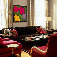 An Andy Warhol flower screenprint hangs behind a chocolate-brown sofa in the living room of a Manhattan apartment where red and brown have been combined to great effect