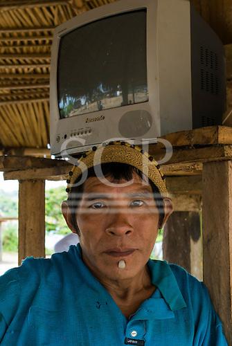 Pará State, Brazil. Aldeia Xingu (Parakana). Cacique Avia Parakaná with the village's television that doesnt work.