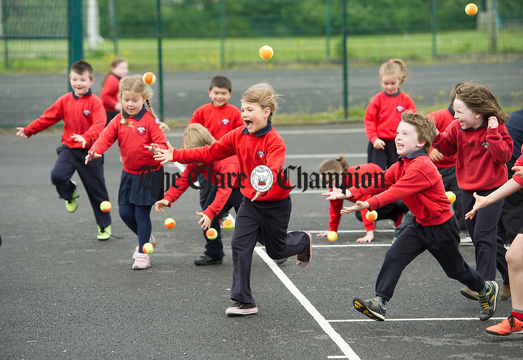Pupils chase tennis balls at a tennis coaching session during a week of sporting activities in Clarecastle NS as part of their Active Schools Flag campaign. Photograph by John Kelly.