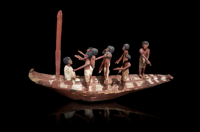 Ancient Egyptian model of a boat with mast, Middle Kingdom (1980-1700 BC. Egyptian Museum, Turin. black background.<br /> <br /> Wooden tomb models were an Egyptian funerary custom throughout the Middle Kingdom in which wooden figurines and sets were constructed to be placed in the tombs of Egyptian royalty.