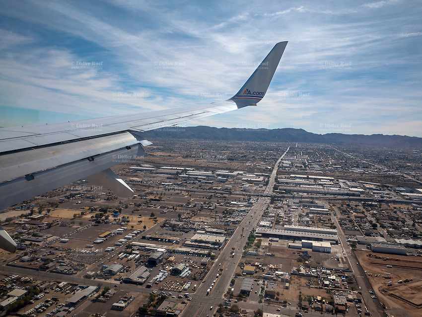 USA. Arizona state. Phoenix. Downtown. View on the wing of an American Airlines plane on his landing approach towards Phoenix airport. American Airlines, Inc. (AA) is a major American airline. Operating an extensive international and domestic network, American Airlines is the world's largest airline by fleet size and revenue, and the second largest by number of destinations served. Phoenix is on of its hubs. 22.01.2016 © 2016 Didier Ruef