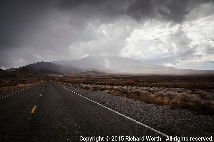 A two-lane highway disappears into the mountains and storm clouds in northern Nevada