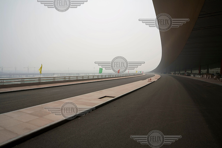 The entrance to Beijing's new airport. A plane comes in to land at the current airport in the distance. The new airport, which is still under construction, was designed by Norman Foster.