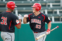 Marcus Knecht #23 of the Canadian World Cup/Pan Am Team is congratulated by teammate Michael Crouse #31 after hitting a home run against Team USA at the USA Baseball National Training Center on September 28, 2011 in Cary, North Carolina.  (Brian Westerholt / Four Seam Images)