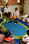 Education preschoool children ages 3-5 female teacher and children in circle time boy demonstrating how a ball bounces lesson on the earth and how it is round vertical