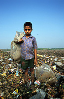 A boy stands among the refuse where he works on the Kajla rubbish dump.  It is one of three landfill sites in this city of twelve million people.  Around 5,000 tonnes of garbage are dumped here each day and over a thousand people work among the rubbish, sorting through the waste and collecting items to sell to retailers for recycling.