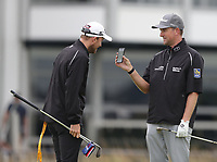 12th July 2021; The Royal St. George's Golf Club, Sandwich, Kent, England; The 149th Open Golf Championship, practice day; Webb Simpson (USA) shows his caddie his phone screen on the 18th green