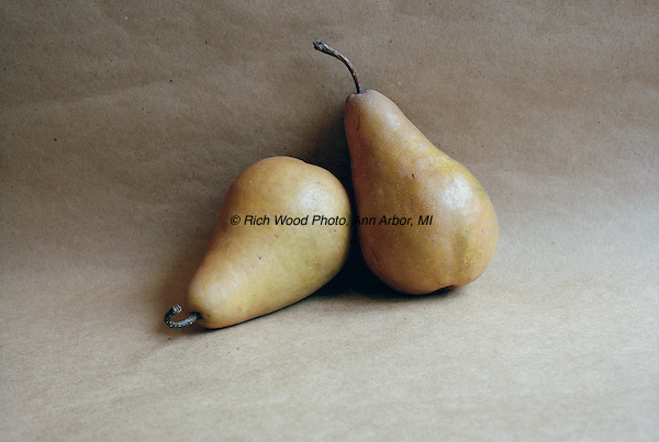 Composed studio rendering of two Bosc pears with natural light and butcher paper background