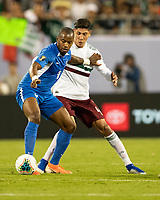 CHARLOTTE, NC - JUNE 23: Kevin Fortune #9 holds off Edson Alvarez #4 during a game between Mexico and Martinique at Bank of America Stadium on June 23, 2019 in Charlotte, North Carolina.