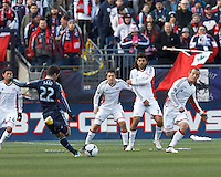 Sporting Kansas City midfielder Soony Saad (22) takes a shot after free kick. The New England Revolution wall: New England Revolution defender Kelyn Rowe (11), New England Revolution forward Juan Toja (7), and New England Revolution forward Chad Barrett (9).  In a Major League Soccer (MLS) match, Sporting Kansas City (blue) tied the New England Revolution (white), 0-0, at Gillette Stadium on March 23, 2013.