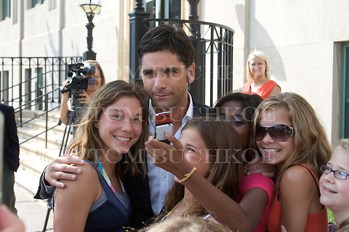 Actor John Stamos visits with fans outside the federal courthouse in Marquette, Michigan during the trial of two people charged with trying to extort money from him.