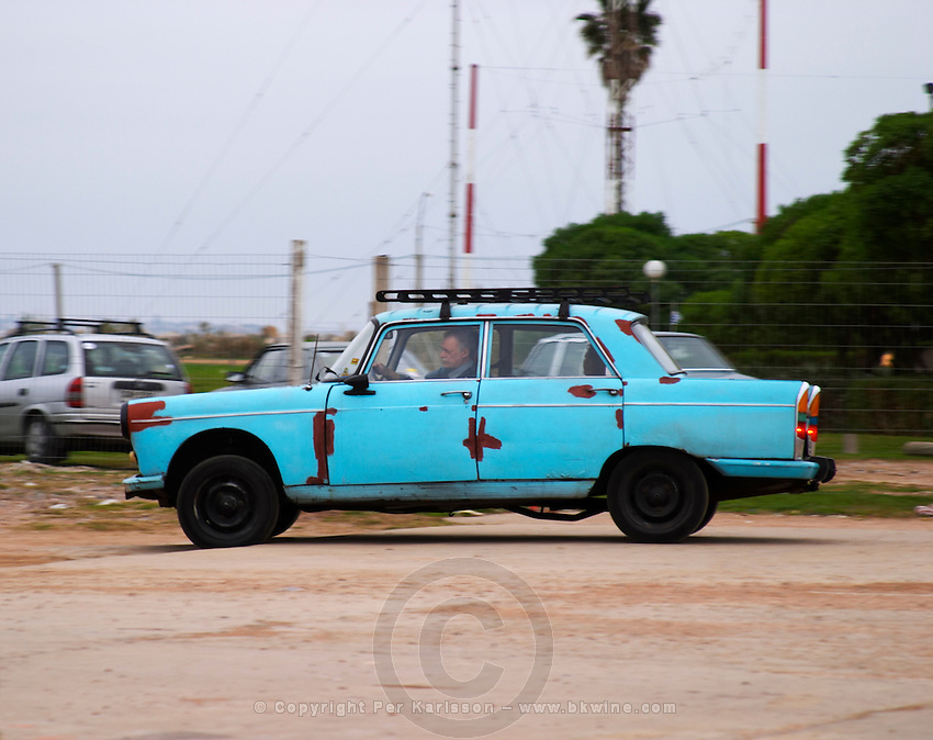 A rusty old 1950s car in blue on a parking lot with a man driving. Montevideo, Uruguay, South America