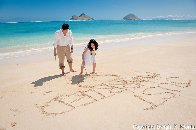 """Asian bride writes """"Just Married"""" in the sand during a stroll on Lanikai beach, Mokulua Islands in the background. The couple celebrate their wedding with a honeymoon in Hawaii."""