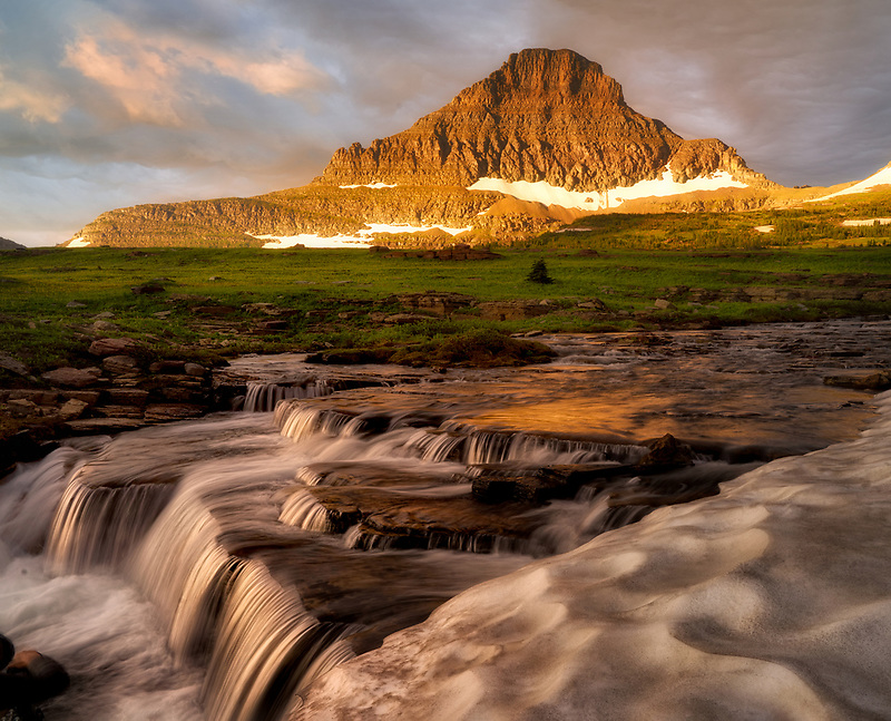 Waterfall along Reynolds Creek at Logan Pass with Mt. Reynolds and snow bank at sunrise, Glacier National Park, Montana