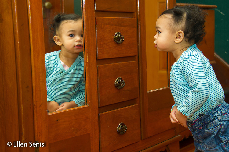 MR / Schenectady, NY. Toddler (1 year and 2 months old, African-American and Caucasian) with a curious expression looks in mirror. MR: Dal4. ID: AM-HD. © Ellen B. Senisi