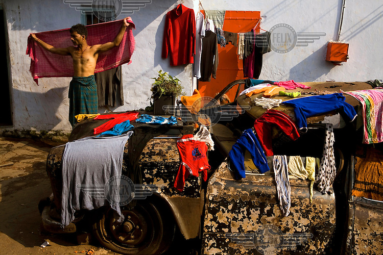 People from Nuatanbazaar dry their wet clothes on an old rusted car in Kolkata.