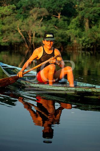 Anavilhanas, Brazil. Man with Brazil baseball cap, singlet and shorts paddling a small one man canoe.