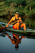 Anavilhanas, Brazil. Man with Brazil baseball cap, singlet and shorts paddling a small one man canoe.